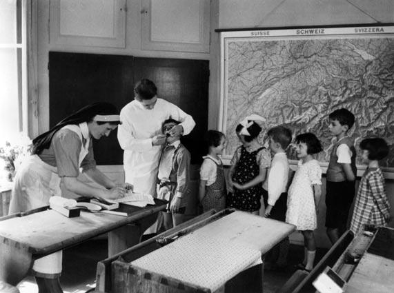 Germaine Golay (volée 1923), lors de la visite du dentiste scolaire. Elle tient les registres médicaux afin d'assurer la suite des traitements, si nécessaire.